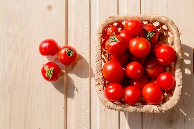 Tomaten, cherry tomaat in de mand op houten tafel