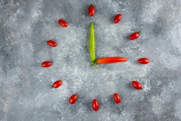 Tomaten en chilipepers vormden zich als een klok op een marmeren oppervlak.