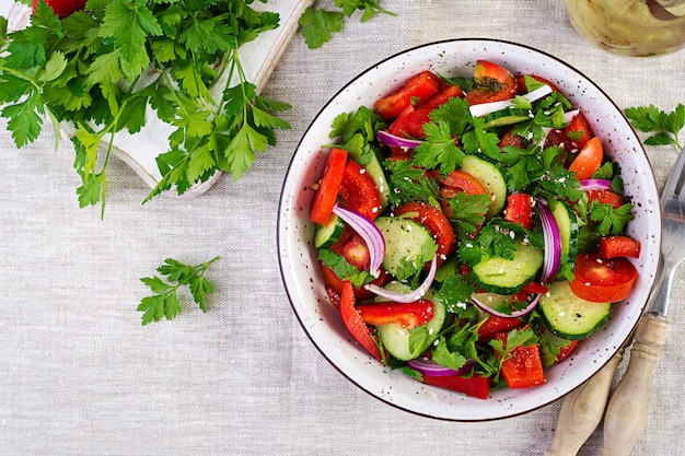 Tomaten- en komkommersalade met rode ui, paprika, zwarte peper en peterselie. veganistisch eten. dieet menu. bovenaanzicht plat leggen