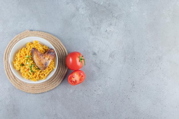 Tomaten en noedelkom op een onderzetter, op de marmeren achtergrond.