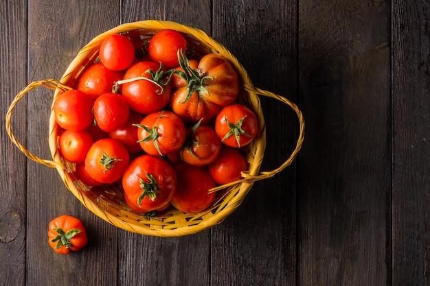 Tomaten geteeld in een moestuin in een rieten mand op een houten tafel
