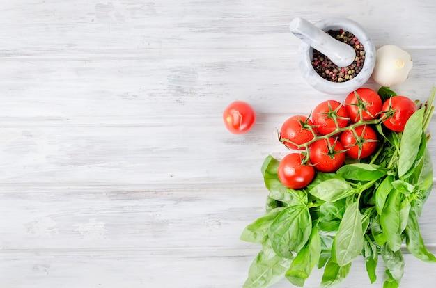 Tomaten, groene basilicum en kruiden in een stenen vijzel