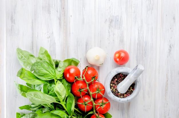 Tomaten, groene basilicum en specerijen in een stenen vijzel