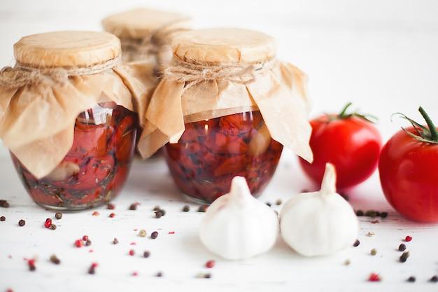Tomaten in de pot. zelfgemaakte zongedroogde tomaten. tijdelijke sluiting. zomer en herfst ingeblikt voedsel. conserveer met kruiden en groenten.