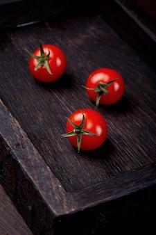 Tomaten in een houten vakje op de houten tafel. tomaten op een houten achtergrond.