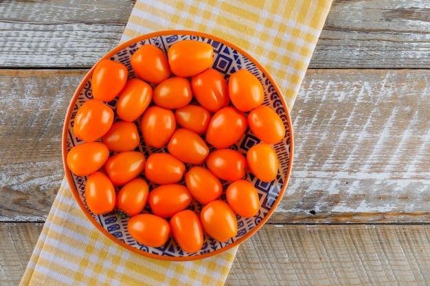 Tomaten in een plaat op houten en keuken handdoek. plat lag.
