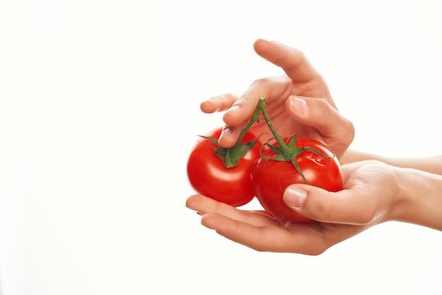 Tomaten in handen op een tak die voedselingrediënten voor de keuken kookt