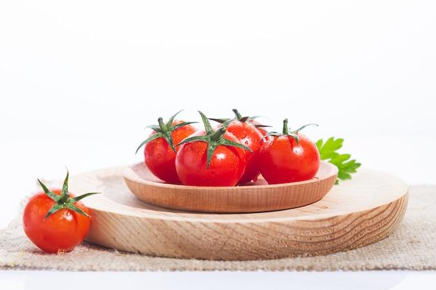 Tomaten in houten plaat op witte achtergrond