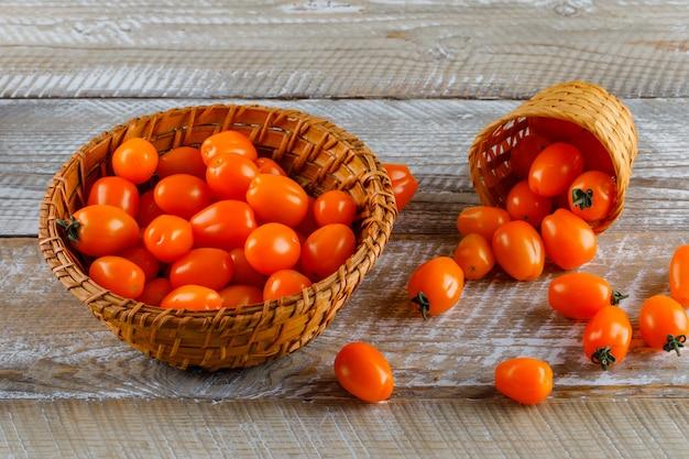 Tomaten in manden op een houten tafel. hoge hoekmening.