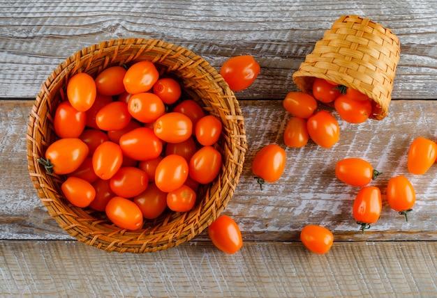 Tomaten in manden op een houten tafel. plat lag.