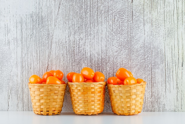 Tomaten in manden op witte en grungy tafel. zijaanzicht.