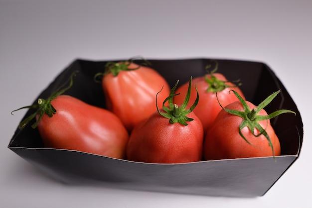 Tomaten in milieuvriendelijke verpakking bos van verse rode tomaten met geïsoleerde groene stengels