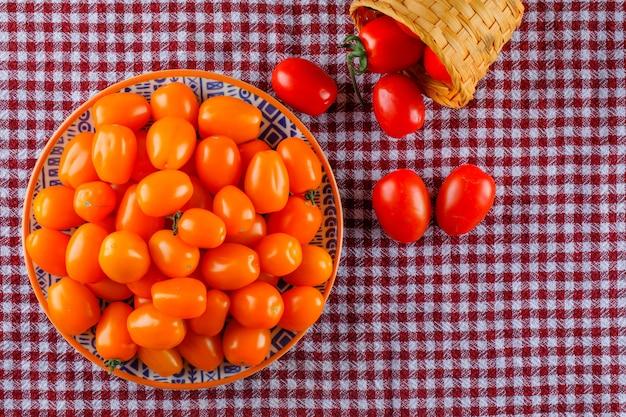 Tomaten in plaat en mand plat lag op een picknick doek
