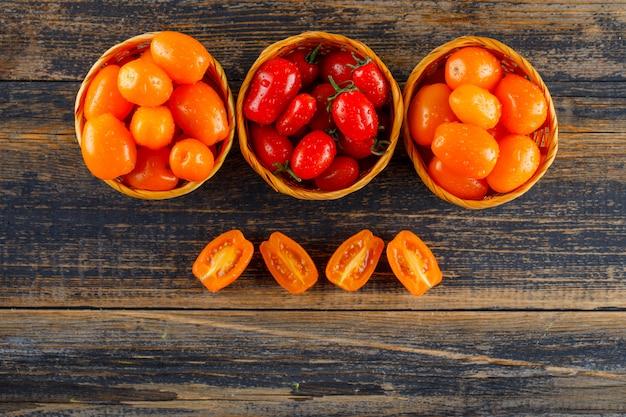 Tomaten in rieten manden op een houten tafel. plat lag.