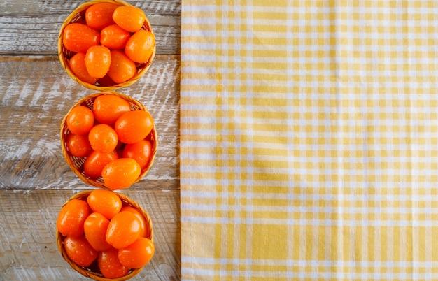 Tomaten in rieten manden plat lag op houten en picknick doek