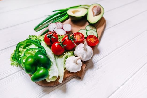 Tomaten, komkommer, knoflook, verse kruiden, radijs, avocado op snijplank. boek met recepten