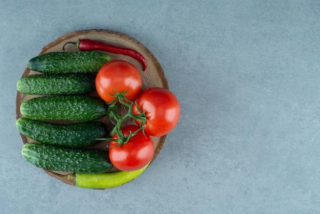 Tomaten, komkommers en peper op houten stuk.