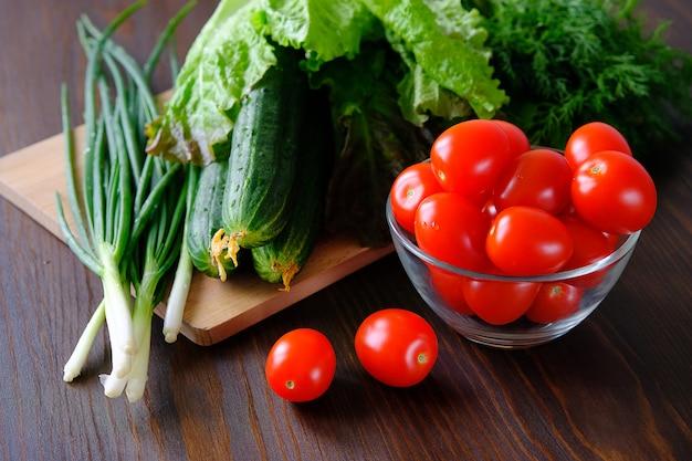 Tomaten, komkommers, groene salade en uien. zelfgemaakte biologische groenten.