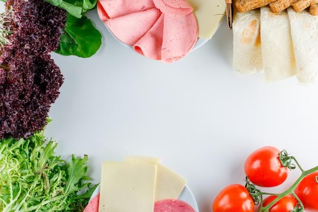 Tomaten met bladgroenten, rode sla, brood, kaas, worst, plat leggen.