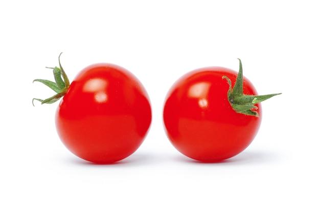 Tomaten met groene bladeren die op witte achtergrond worden geïsoleerd
