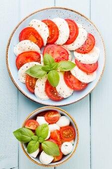 Tomaten, mozzarellakaas, basilicum en kruiden op grijs leisteen bord. italiaanse traditionele caprese salade ingrediënten.