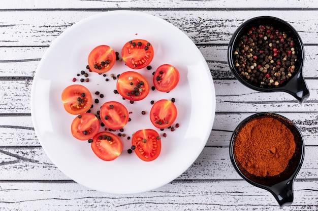 Tomaten op een witte plaat met peper poeder bovenaanzicht