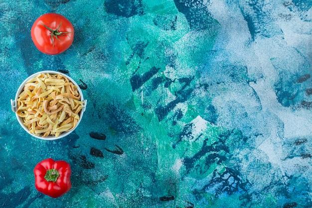 Tomaten, paprika en zelfgemaakte noedels in een emmer, op de blauwe achtergrond.