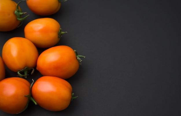 Tomaten plat lag op zwart. stilleven food fotografie. excentrische compositie, kopieer ruimte.