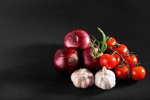 Tomaten, uien en knoflook zijn geïsoleerd op een zwarte