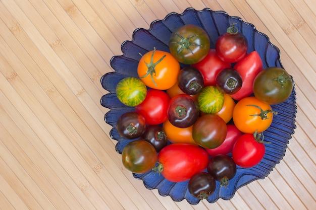 Tomaten van verschillende kleuren in blauwe vaas. houten oppervlak van bamboe.