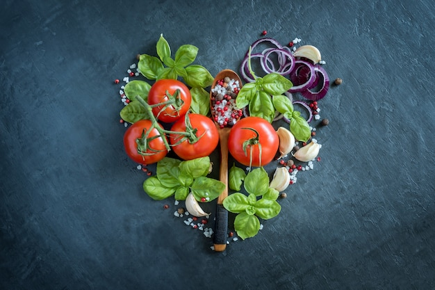 Tomatenbasilicum knoflook en kruiden op een steenlijst in de vorm van concept van het hart het gezonde voedsel.