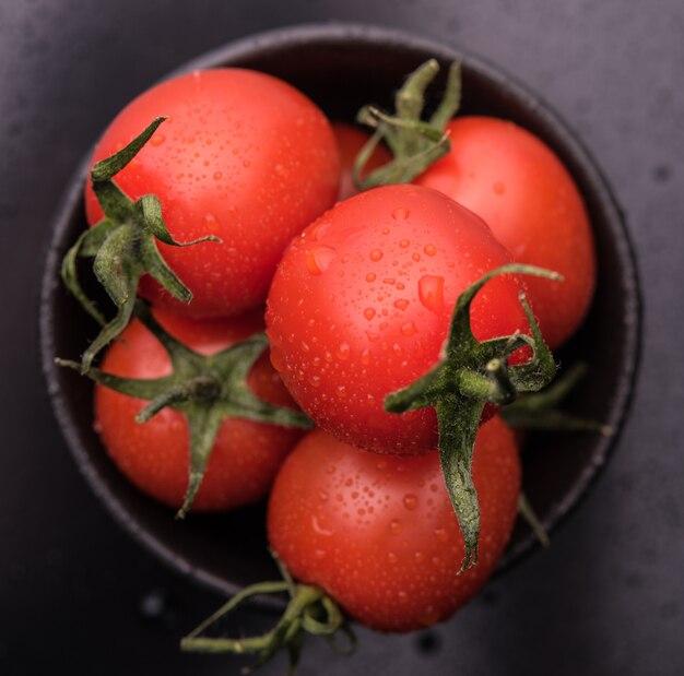 Tomatenkers in kom, donkere foto bovenaanzicht
