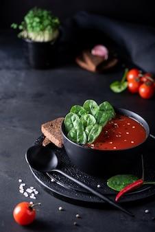 Tomatenpuree soep met spinazie in een zwarte kom, close-up Premium Foto