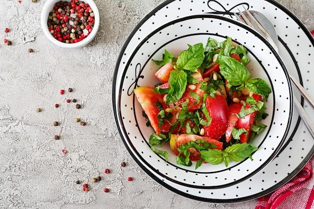 Tomatensalade met basilicum en pijnboompitten in kom - gezond vegetarisch veganistisch dieet biologisch voedsel voorgerecht. bovenaanzicht. plat liggen