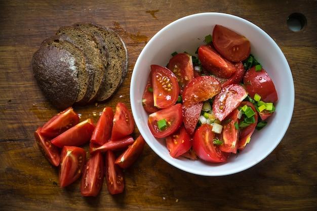 Tomatensalade met olijfolie en balsamico-azijn in kom over houten achtergrond