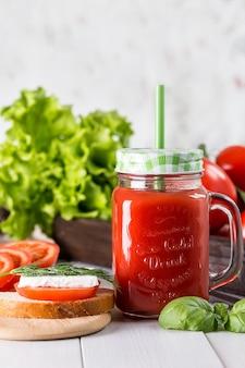 Tomatensap in een doorzichtige pot met spinazie