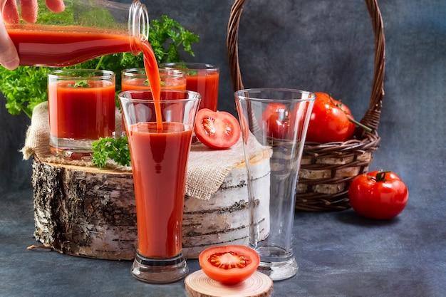 Tomatensap wordt uit een fles in een glas gegoten