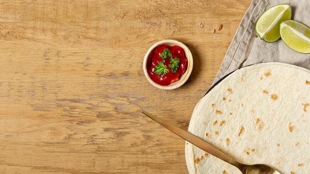 Tomatensaus in de buurt van lepel en tortilla met gesneden limoen