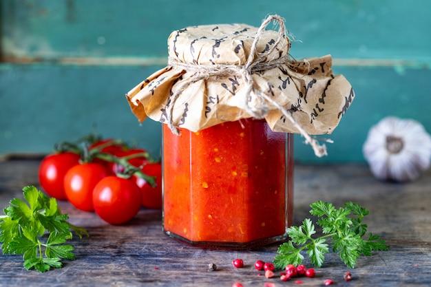 Tomatensaus in een glazen pot en ingrediënten, close-up, horizontaal