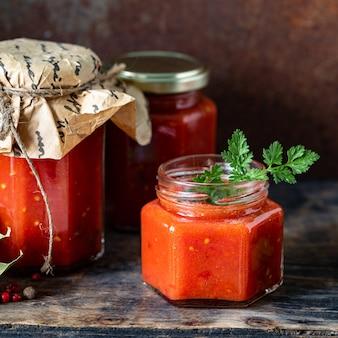 Tomatensaus in een glazen pot en ingrediënten, close-up. vierkant