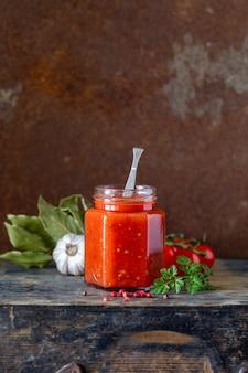 Tomatensaus in een glazen pot en ingrediënten. kopieer ruimte