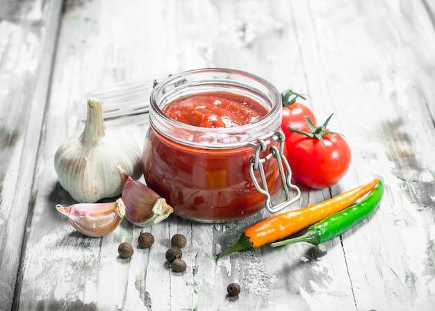 Tomatensaus in een pot en kruiden.