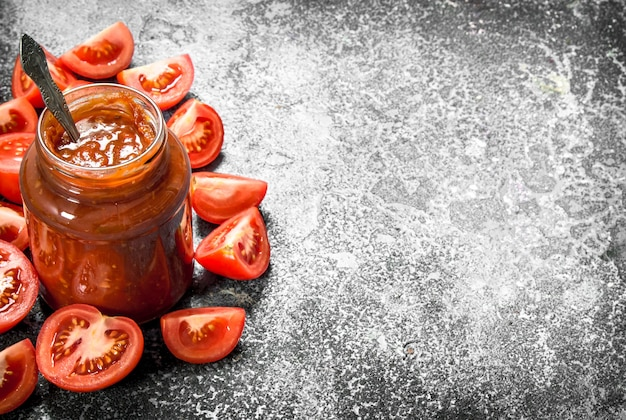 Tomatensaus in glazen pot met lepel. op rustieke achtergrond.
