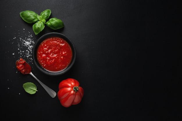 Tomatensaus in kom met basilicumzout op donkere ondergrond