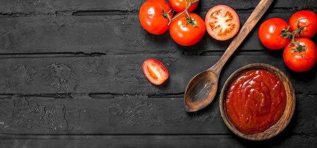 Tomatensaus in kom met spoonnd rijpe tomaten op zwarte rustieke tafel