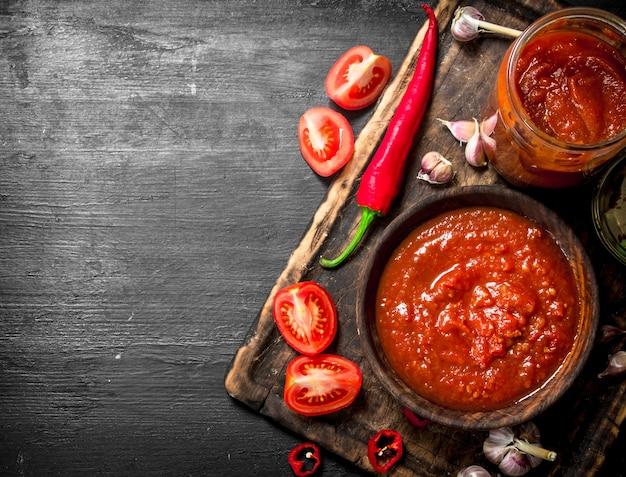 Tomatensaus met knoflook en hete pepers aan boord op zwart bord.