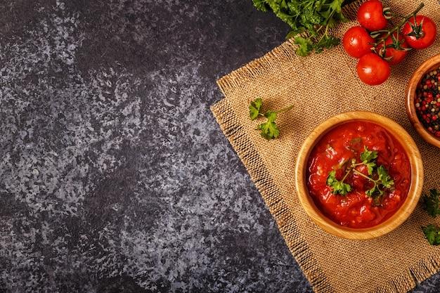Tomatensaus met knoflook en peterselie in een houten kom