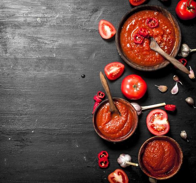 Tomatensaus met knoflook in houten kommen. op zwart bord.
