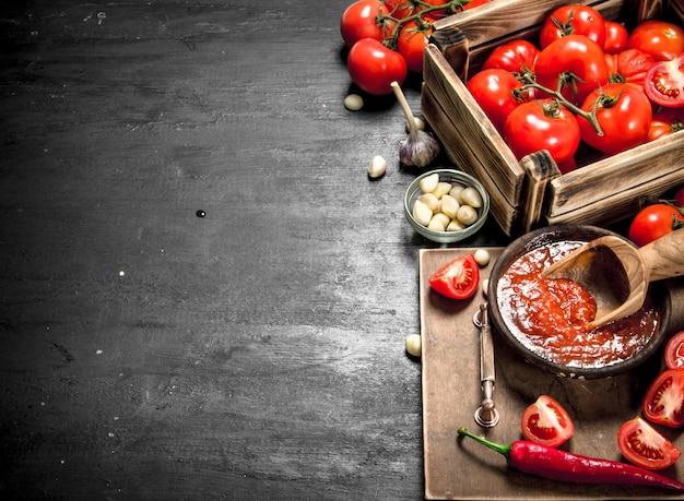 Tomatensaus met kruiden, hete peper en knoflook. op zwart bord.