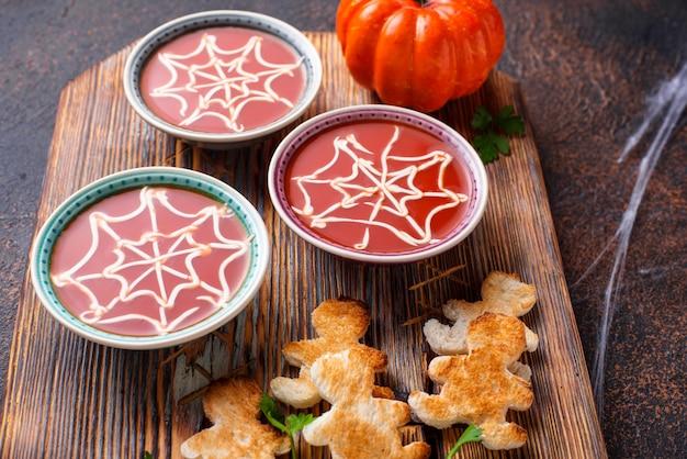 Tomatensoep en brood in de vorm van mannen. halloween-traktaties voor feest.